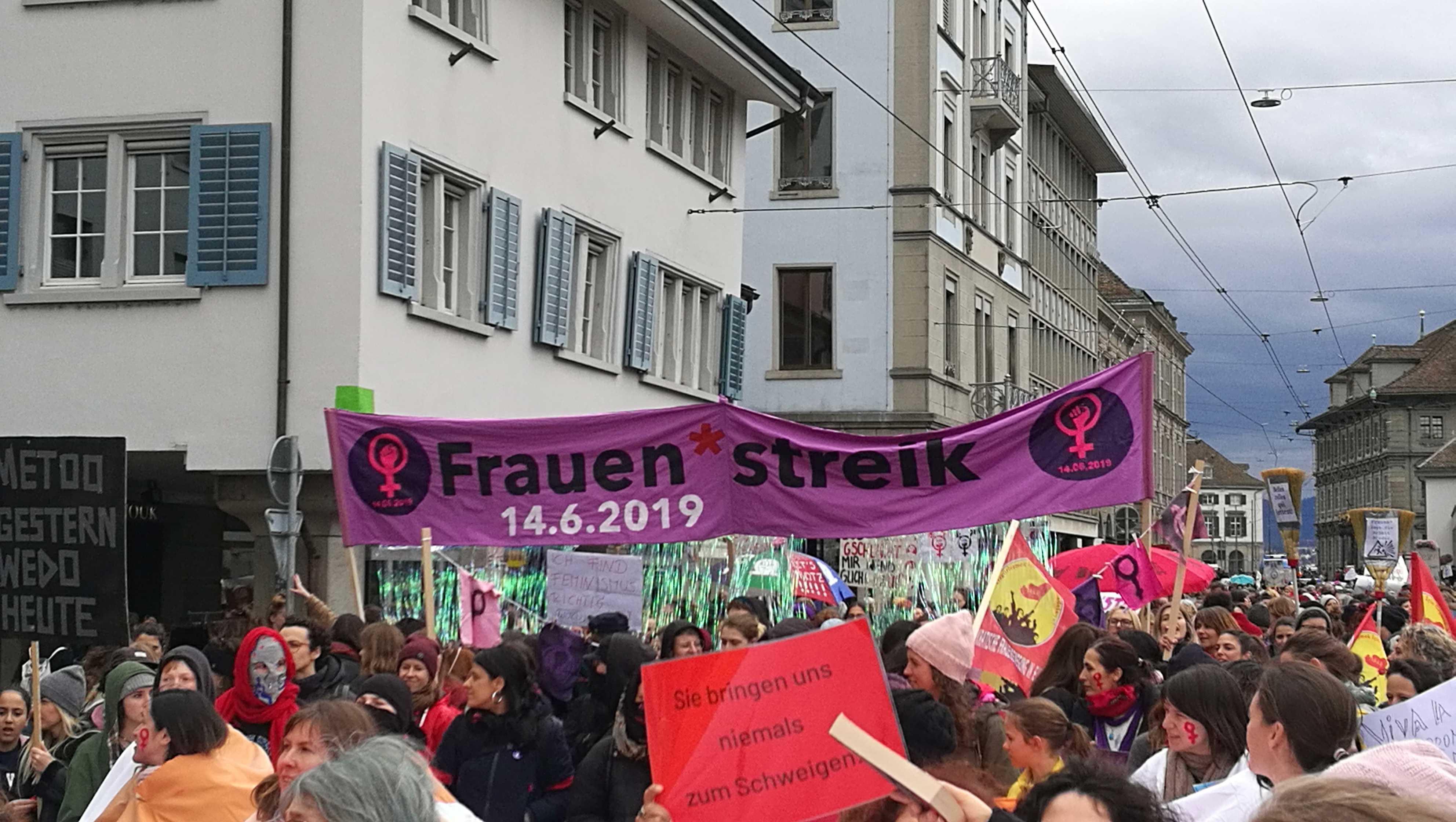 """Foto von der Demonstration am 8. März in Zürich, zu sehen ist das Hochtransparent des Frauen*streikkollektivs Zürich, auf dem steht Frauen*streik 14.6.2019. Darum herum ganz viele Frauen und weiter Plackarden. Im Vordergrund eines auf dem steht """"Sie bringen uns niemals zum Schweiten"""""""