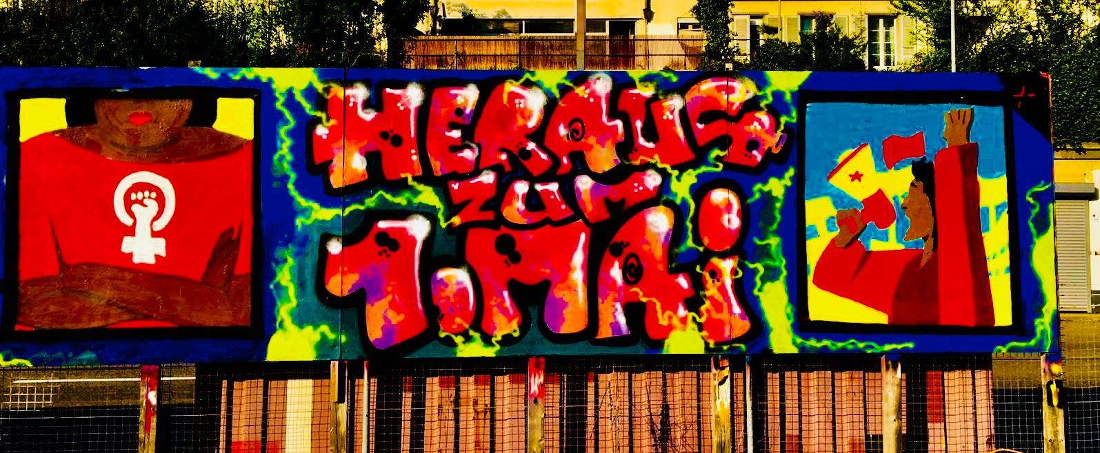 """Foto eines Wandbildes zum 1. Mai: In der Mitte der Text """"Heraus zum 1. Mai"""". Links eine gesprayte Zeichnung einer POC mit verschränkten Armen und einem roten Shirt mit dem Feministmus Symbol mit Faust. Rechts eine gespryte Zeichnung einer Person mit erhobener Faust, die Vor dem Hintergrund einer angedeuteten Demonstation in ein gelebes Megaphon mit rotem Stern schreit."""