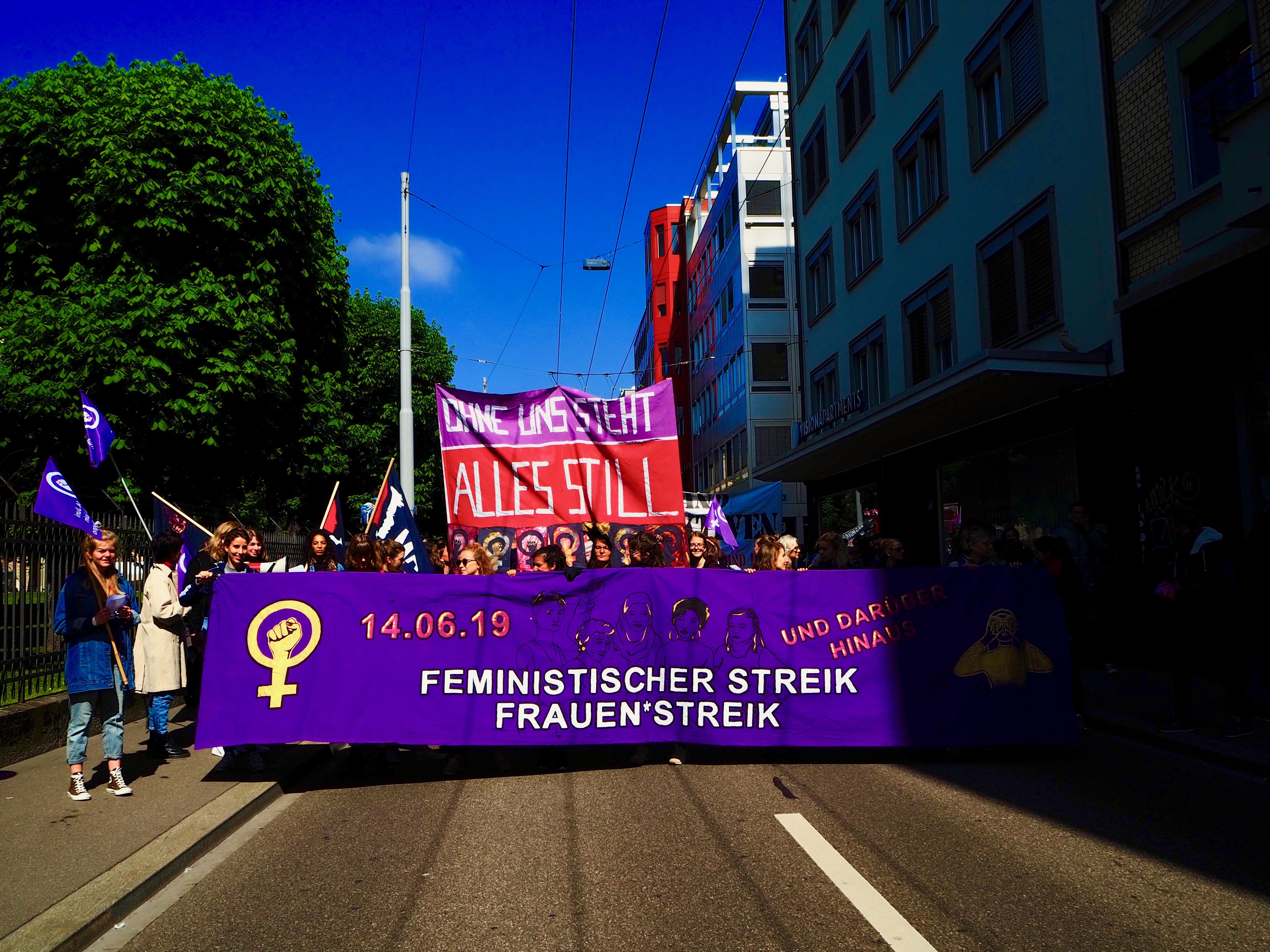 """Foto vom Fronttransparent des Frauen*streikblocks. Darauf steht """"Feministischer Strei / Frauen*streik 14.Juni 2019"""" Dahinter ein Transparent wo draufsteht """"Ohne uns steht alles still""""."""