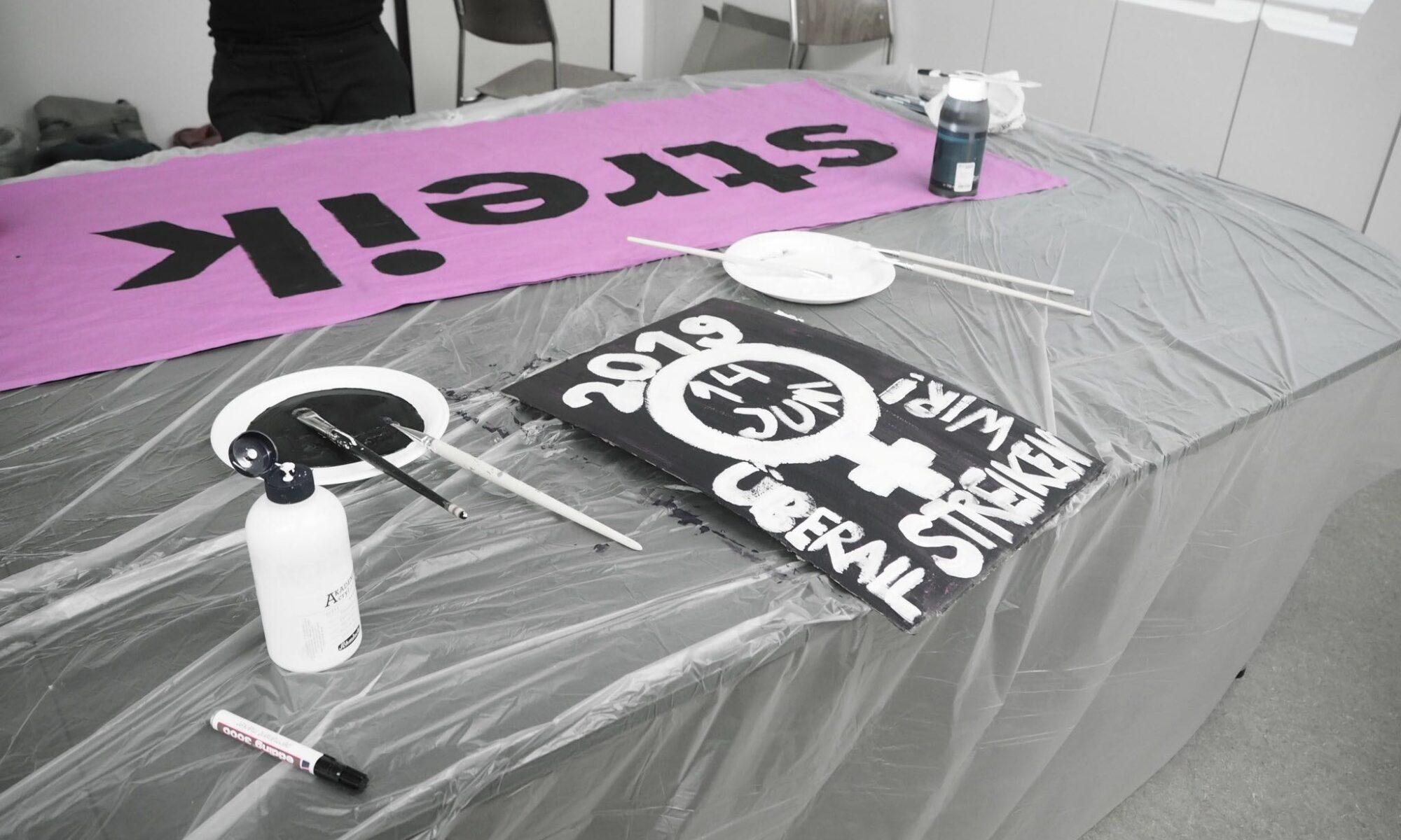 """Foto von einer Transpimalen-Session, zu sehen sind Pinsel, bemalter Karton und ein Teil des bemalten Transparents, auf dem """"Streik"""" steht"""