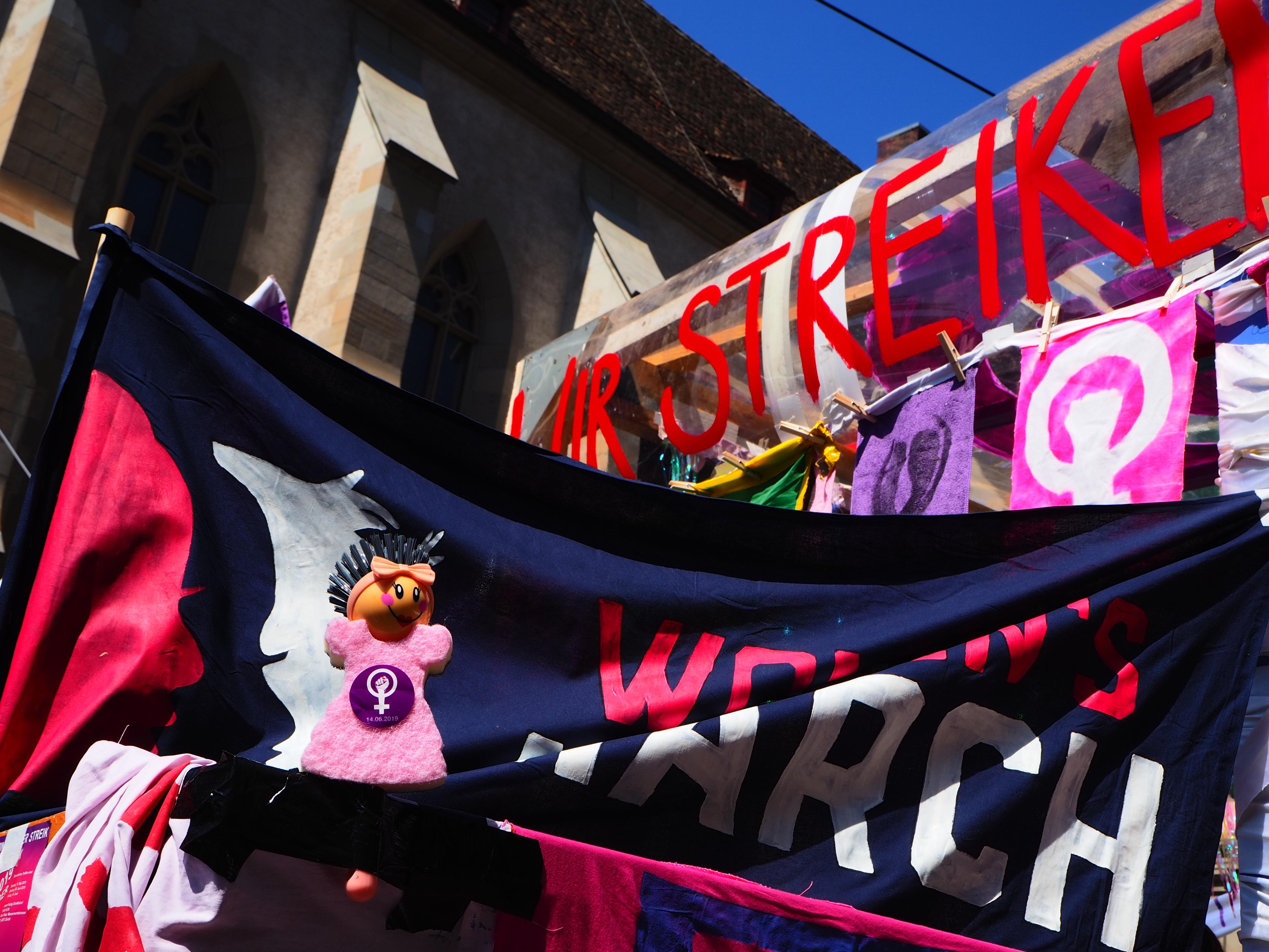 Foto vom Frauen*streikkblock am 1. Mai. Viele Transparente und zuvorderst Violetta, eine Geschirrspülbürste in Form einer Frau mit einem Schwammkleid, die befreut wurde und nun Teil des Streikkollektivs ist.