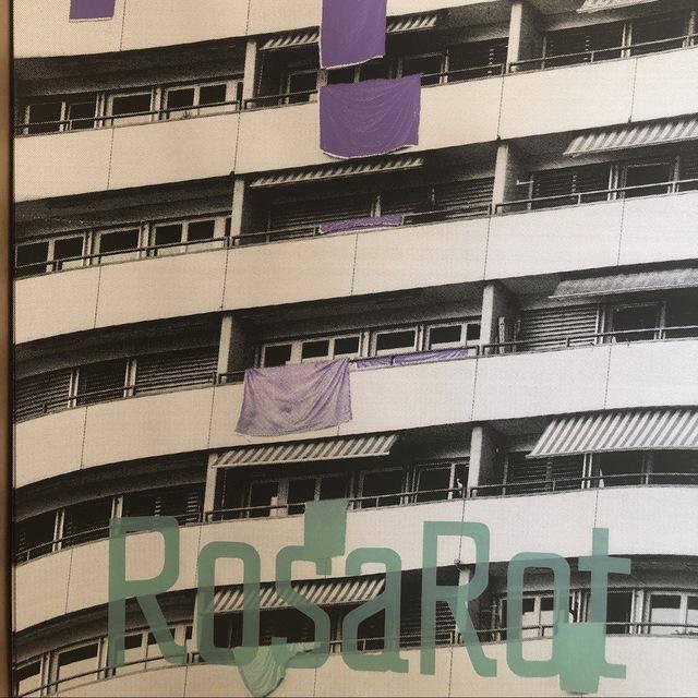 Hausfassade mit vielen Balkonen von denen Violette Tücher herunterhängen
