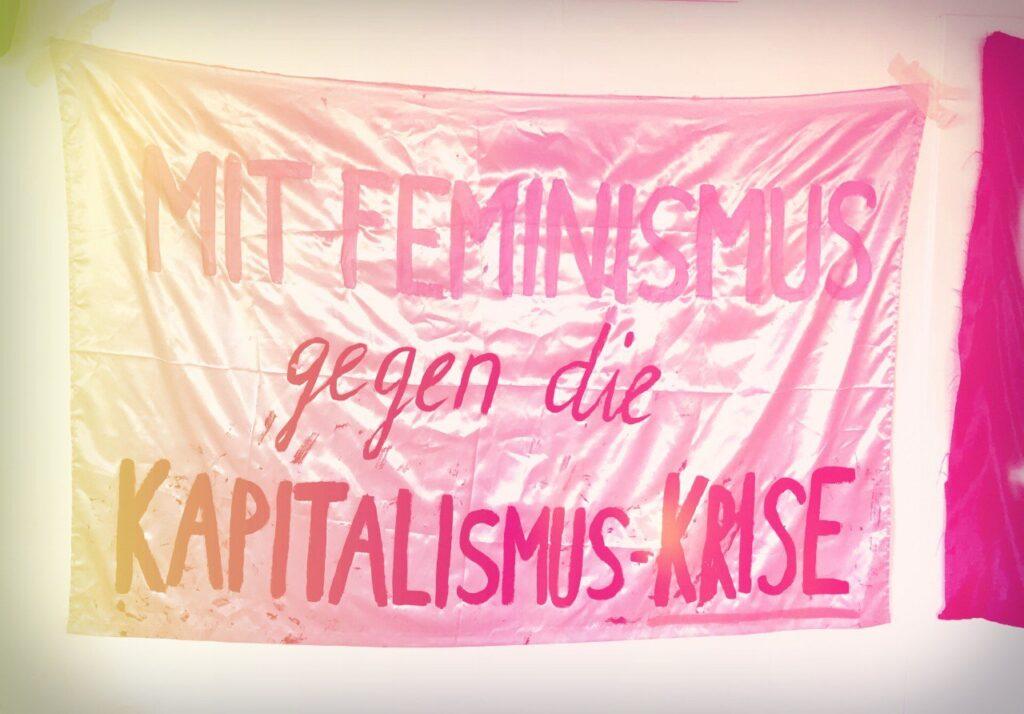 """Foto eines Transparentes uaf dem steht """"Mit Feminismus gegen die Kapitalismus-krise"""""""