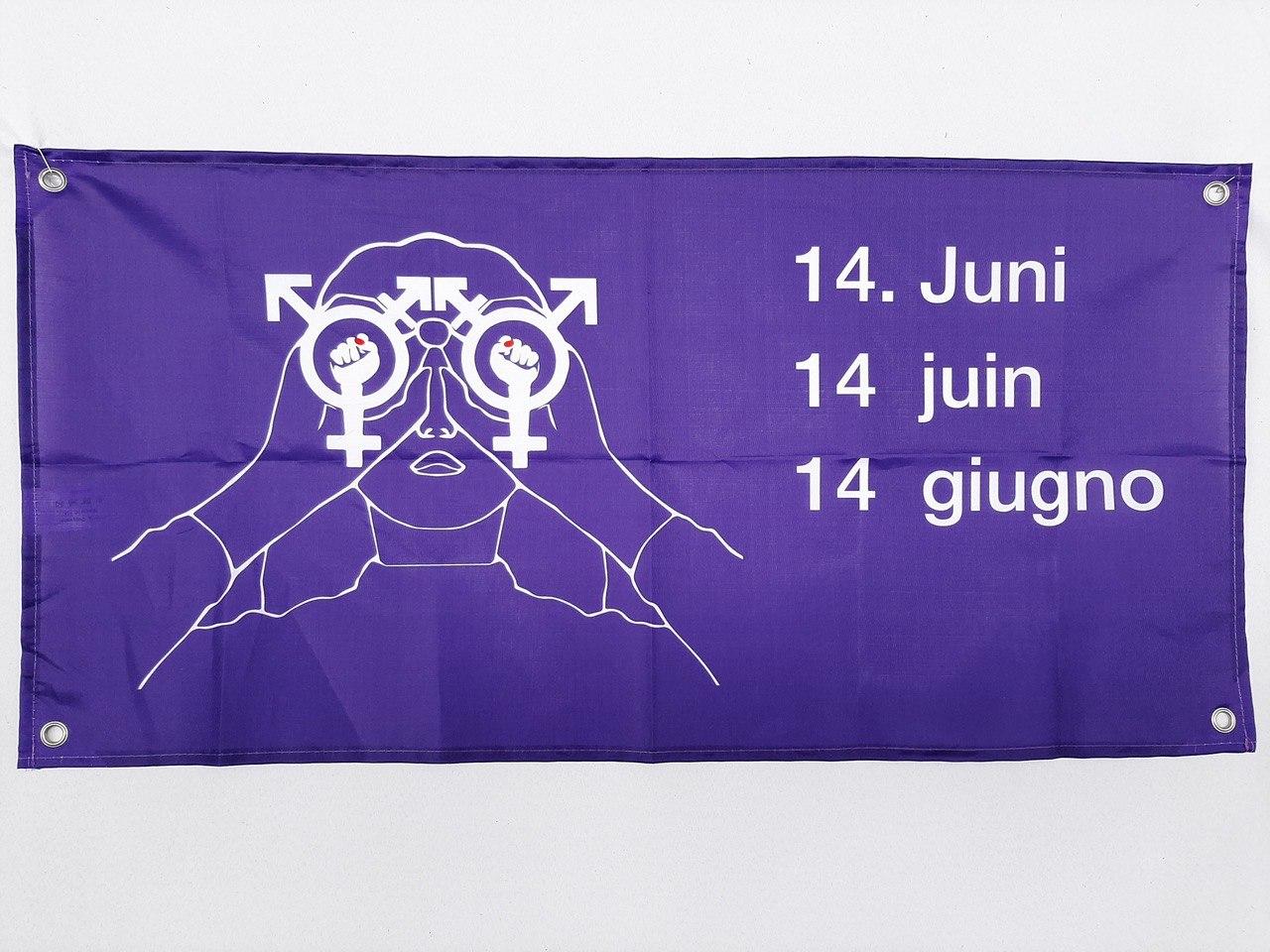 Foto einer Fahne mit dem Logo einer Weiblichen Person die durch einen intersektionalfeministischen Feldstecher schaut, daneben steht 14. Juni 14 juin 14giugno in weiss auf violettem stoff mit vier lochösen in jeder Ecke